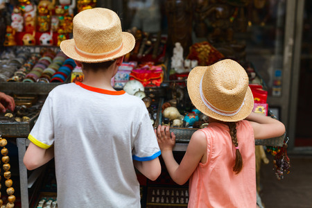 Back view of two kids brother and sister at flea market Foto de archivo