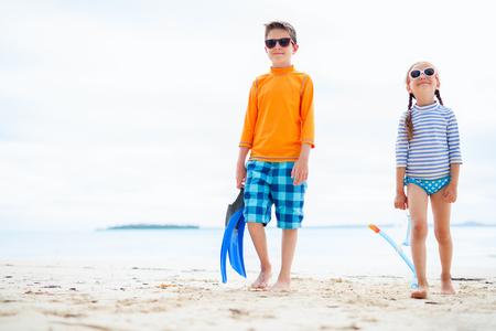 proteccion: Los ni�os peque�os en erupci�n guardias para protegerse del sol con el equipo de snorkel en la playa tropical durante las vacaciones de verano