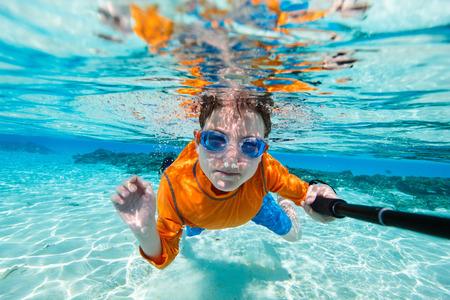 熱帯のビーチで浅いの青緑色の水で水中の selfie を作るかわいい 10 代の少年 写真素材