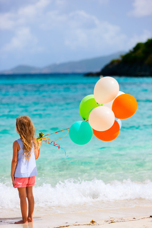 aviators: Back view of little girl with colorful balloons at beach during summer vacation