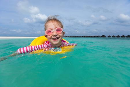 schwimmring: Der entzückende kleine Mädchen mit gelben aufblasbaren Ring Schwimmen in einem tropischen Meer in den Sommerferien Lizenzfreie Bilder