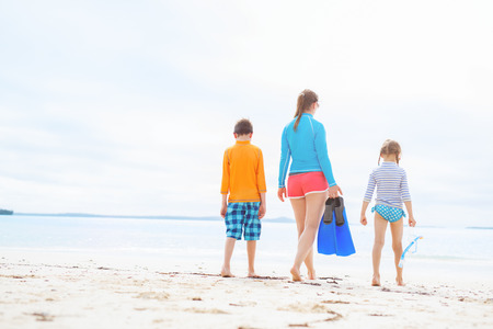 family vacation: Family of mother and kids with snorkeling equipment enjoying beach vacation