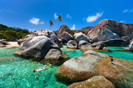 virgin girl: Young woman snorkeling in turquoise tropical water among huge granite boulders at The Baths beach area major tourist attraction on Virgin Gorda, British Virgin Islands, Caribbean Stock Photo