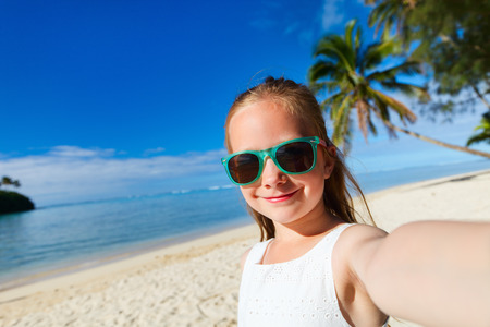 rarotonga: Adorable little girl making selfie in at tropical beach on Rarotonga island during summer vacation