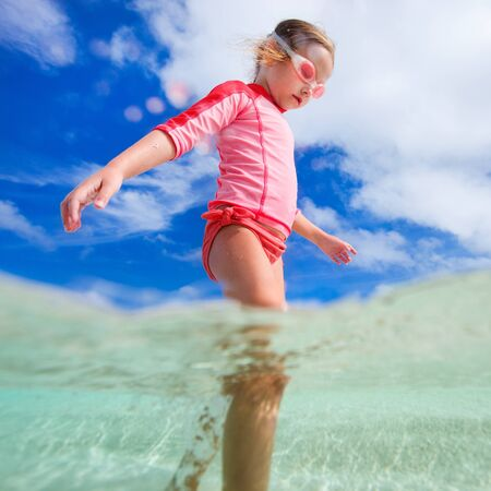 cute little girl: Adorable little girl at shallow water on tropical beach