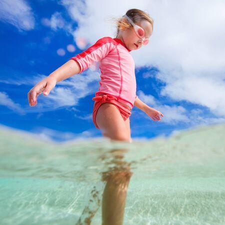 mignonne petite fille: Adorable petite fille à l'eau peu profonde sur la plage tropicale