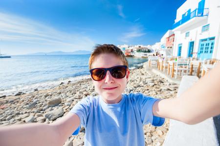 'teenager boy: Cute teenage tourist making selfie at Little Venice area on Mykonos island, Greece Stock Photo