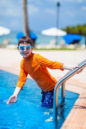 sun protection: Cute boy wearing sun protection swimwear at pool