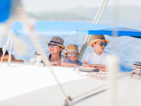 Mother and her kids having great time sailing at luxury yacht or catamaran boat 写真素材