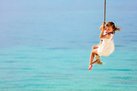 columpios: Niña que se divierte de balanceo en una cuerda en la playa de isla tropical