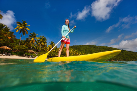 paddling: Active young woman on tropical beach vacation paddling on stand up board Stock Photo