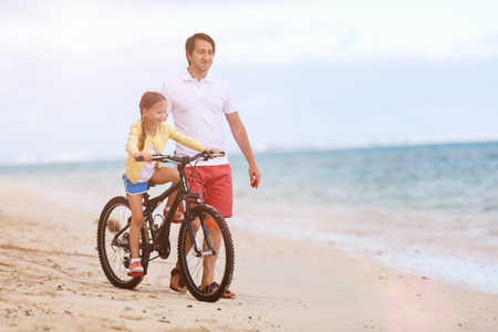 kids playing beach: Father teaching her little daughter to ride a bike at the beach having fun together