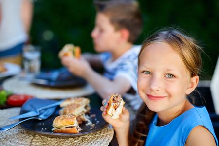 Förtjusande liten tjej och hennes familj äter läckra hemlagad burger utomhus på sommardagen Stockfoto