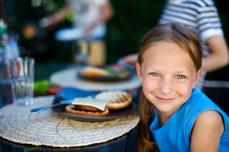 niñas bonitas: Niña adorable y su familia comiendo deliciosa hamburguesa casera al aire libre en día de verano Foto de archivo
