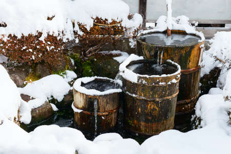 water town: Wooden barrels filled with water and snow, close up details of old district at historical Takayama town in Japan on winter day