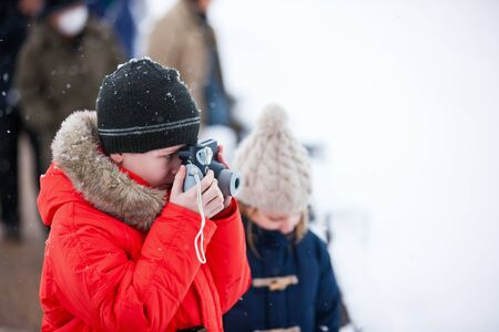winter photos: Cute boy in a red parka down jacket outdoors on beautiful winter snow day taking photos with small camera