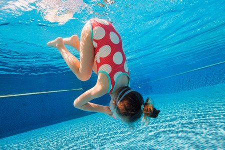 enjoyment: Underwater photo of adorable little girl diving and swimming in pool on summer vacation Stock Photo