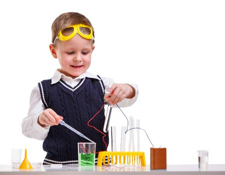 young boy: Young boy performing chemistry experiments with different liquids. Stock Photo