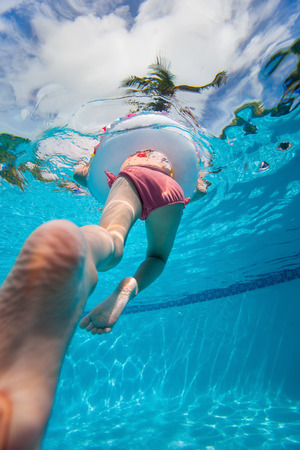 splash pool: Father holding his little daughter feet while she swims in pool Stock Photo