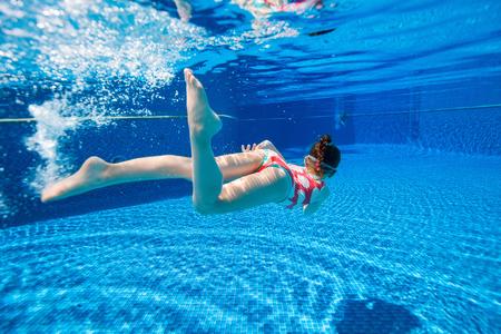 dive: Fotograf�a submarina de buceo poco adorable ni�a y nadar en la piscina en vacaciones de verano Foto de archivo