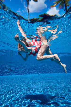 girl underwater: Underwater photo of adorable little girl diving and swimming in pool on summer vacation Stock Photo
