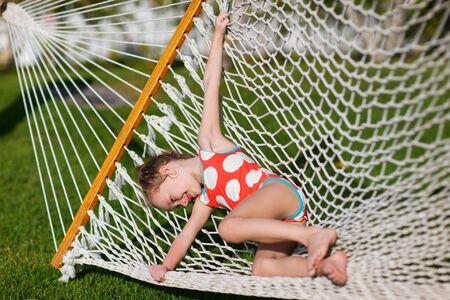 traje de bano: Niña adorable riendo de caer el amanecer en una hierba de hamaca Foto de archivo