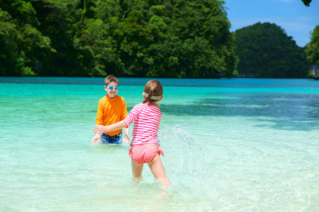 shallow water: Two kids playing at shallow water during summer vacation Stock Photo