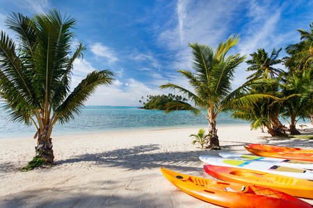 south pacific ocean: Kayaks at beautiful tropical beach with palm trees, white sand, turquoise ocean water and blue sky at Cook Islands, South Pacific