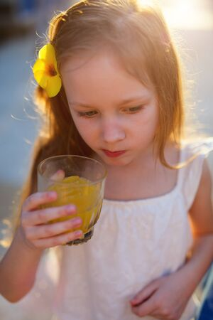 tomando jugo: Adorable little girl drinking juice from a glass