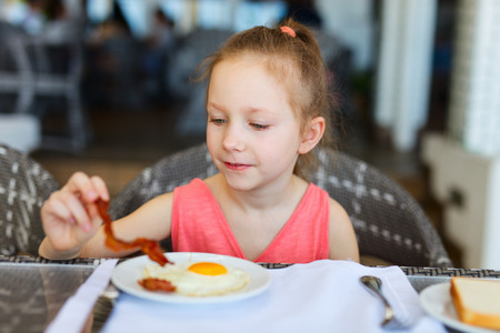 bacon portrait: Adorable little girl eating fried egg for a breakfast in restaurant