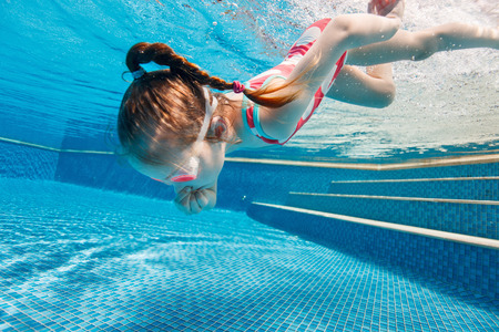 Underwater photo of adorable little girl diving and swimming in pool on summer vacation Archivio Fotografico