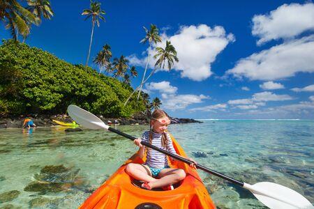 niñas pequeñas: Niña que disfruta remar en kayak colorido naranja en el agua del océano tropical durante las vacaciones de verano