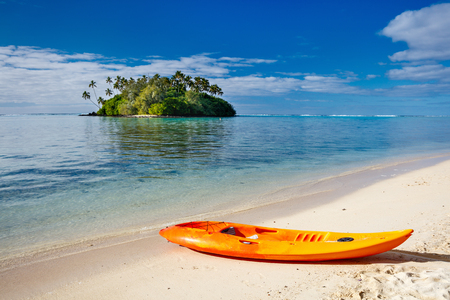 south pacific ocean: Colorful kayak at beautiful tropical beach with palm trees, white sand, turquoise ocean water and blue sky at Cook Islands, South Pacific
