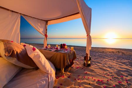 parejas romanticas: Cena romántica y ajuste de lujo en la playa tropical en la puesta del sol