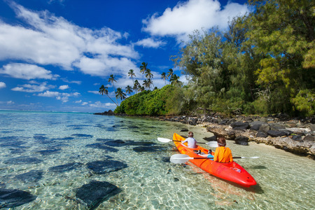 ocean kayak: Los ni�os disfrutan de remar en kayak de color amarillo vivo en el agua del oc�ano tropical durante las vacaciones de verano Foto de archivo