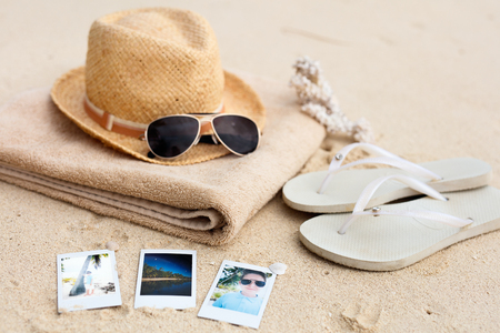 Straw hat, towel, sun glasses, flip flops and instant photos on a tropical beach Stockfoto