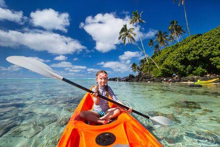 ocean kayak: Ni�a que disfruta remar en kayak colorido naranja en el agua del oc�ano tropical durante las vacaciones de verano