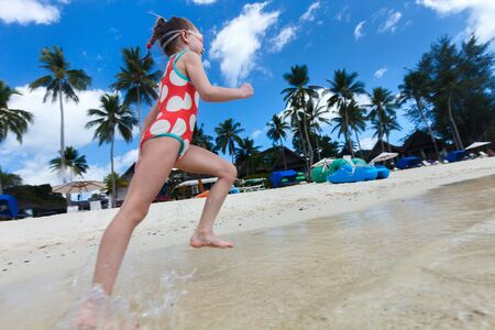 unrecognisable person: Happy little girl running and splashing at shallow water at beach having a lot of fun on summer vacation