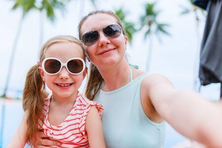 mama e hija: Madre de familia feliz y su pequeña hija adorable en vacaciones de verano tomando Autofoto con smartphone