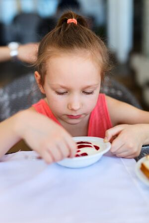 mealtime: Adorable little girl eating breakfast in restaurant Stock Photo