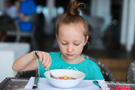 niña comiendo: Niña adorable que come cereal con leche para el desayuno en el restaurante