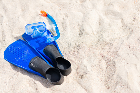 a hobby: Snorkeling equipment mask, snorkel and fins on sand at beach