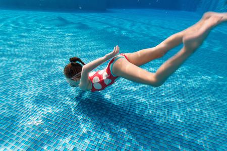 traje de bano: Fotografía submarina de buceo poco adorable niña y nadar en la piscina en vacaciones de verano Foto de archivo