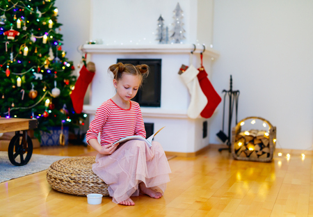 the girl in stockings: Adorable little girl at home beautifully decorated for Christmas with fireplace, tree, stockings and lights