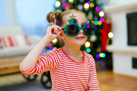 funny glasses: Adorable little girl wearing funny Christmas glasses in home beautifully decorated with Christmas tree and lights Stock Photo