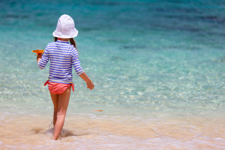 shore: Little girl in a colorful sun protection swimwear on vacation splashing in a shallow water at tropical beach