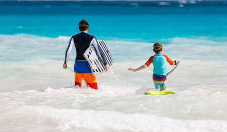boogie: Father and son running towards ocean with boogie boards
