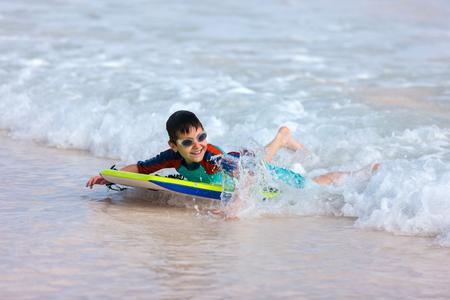 bodyboard: Little boy on vacation having fun swimming on boogie board