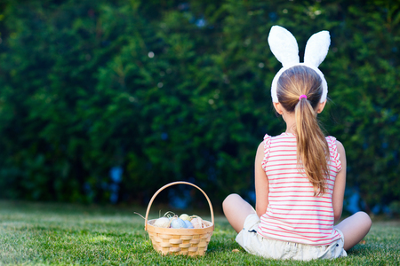 view girl: Back view of a  little girl wearing bunny ears with a basket of colorful Easter eggs outdoors on spring day Stock Photo