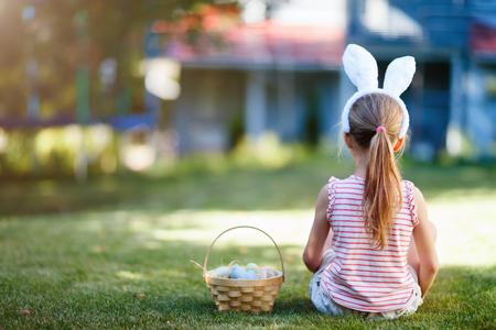 Back view of a  little girl wearing bunny ears with a basket of colorful Easter eggs outdoors on spring day Foto de archivo